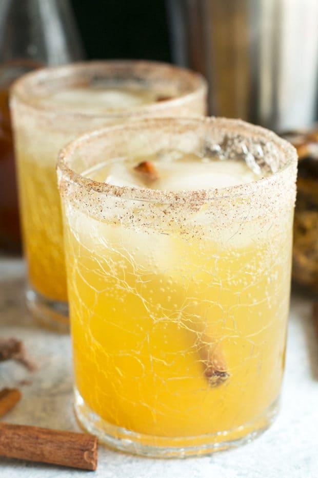 Two Bourbon Pumpkin Smash cocktails with a cinnamon stick