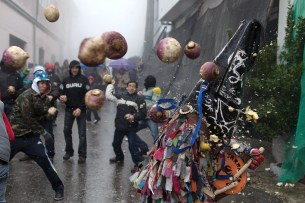 Piornal, Spain: people throw turnips at the folkloric figure of El Jarramplas – a ritual believed to symbolise the expulsion of everything bad – as he makes his way through the streets beating his drum during the Jarramplas festival on January 22, 2013. (Photo by Pablo Blazquez Dominguez)