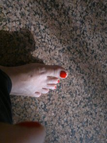 An unevenly-cut-painted-red toe nail