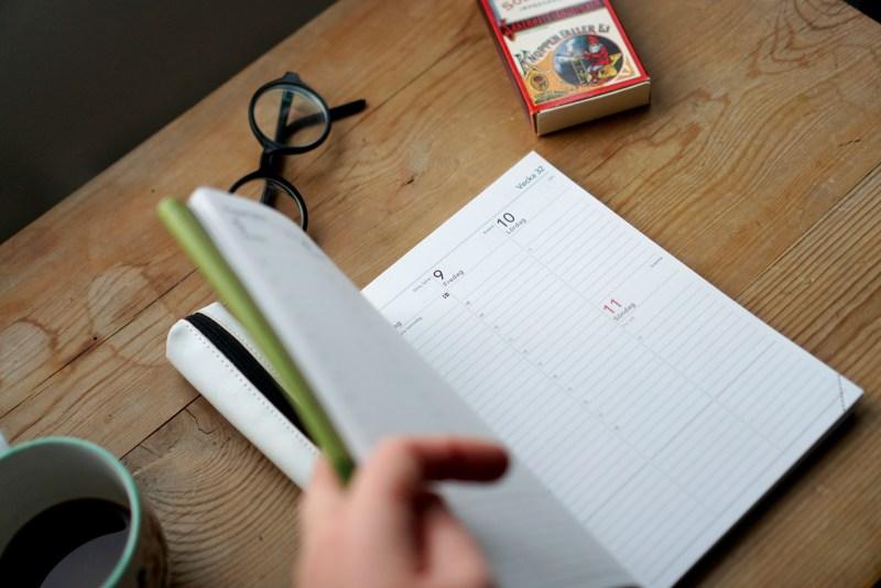 bild på grön almanacka_glasögon pennfodral tändsticksask, kaffekopp, hand