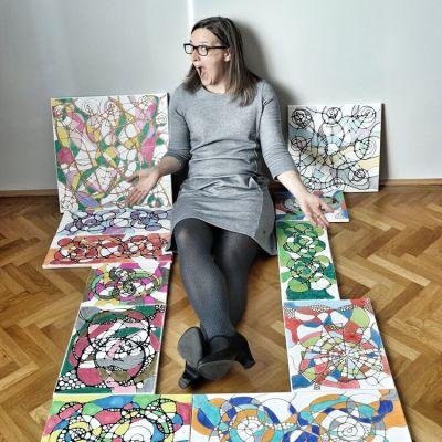 Junge Frau sitzt am Boden an der Wand gelehnt. Um sie herum liegen lauter verschiedene NEURODINGS® Bilder. Beispielbild für die Vielfältigkeit von neurokreativem Zeichnen.