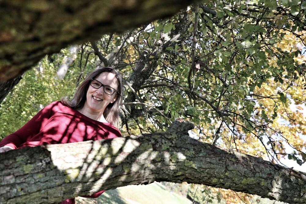 Energiearbeit ist für mich Teil des Lebens geworden. Junge Frau sitzt in einem Baum und lächelt in die Kamera.