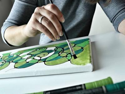 Hand einer jungen Frau mit einem Pinsel. Sie malt ein Neurodings auf Leinwand.