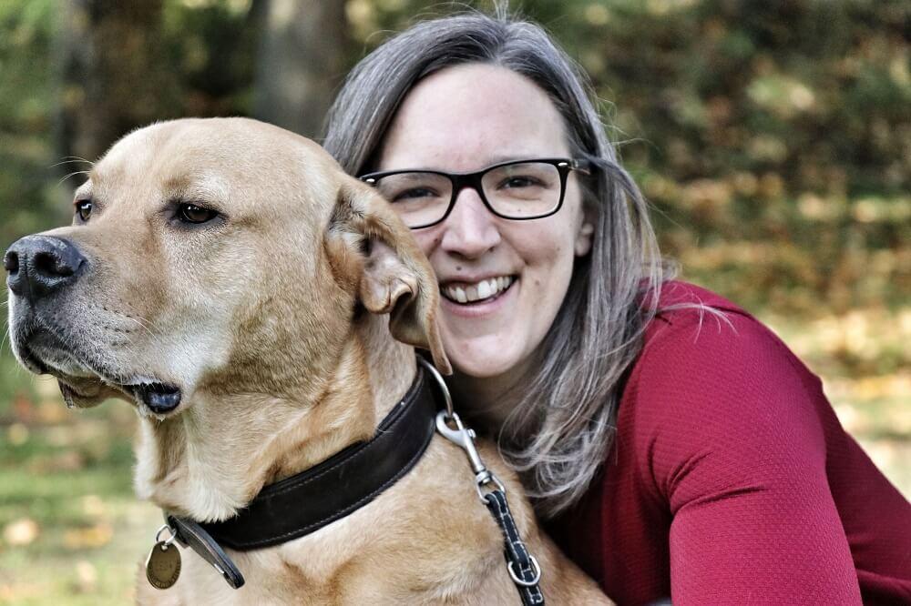 Junge Frau hockt hinter einem Hund und lächelt in die Kamera