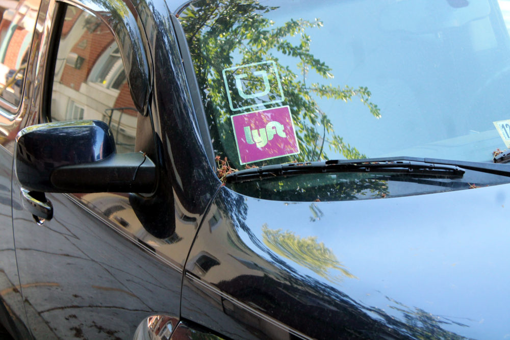 a car windshield with Uber and Lyft stickers