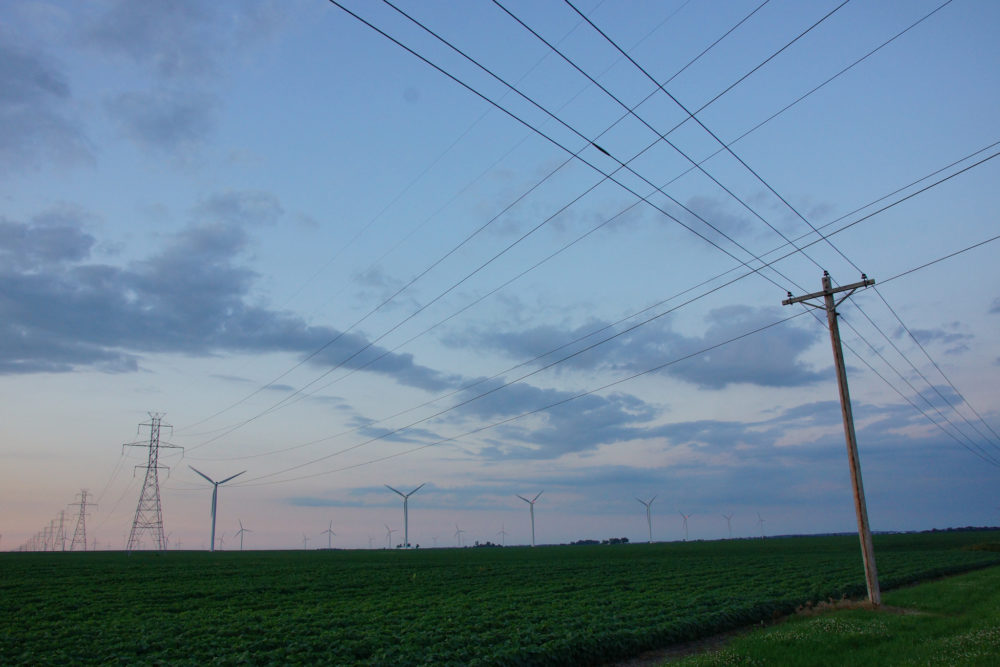 crisscrossing power lines with wind turbines in the distance