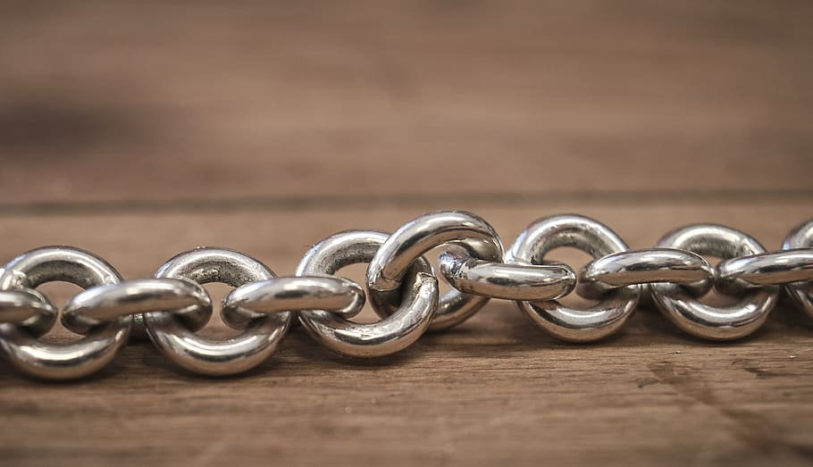 a chain of circular silver links rest on a wooden surface