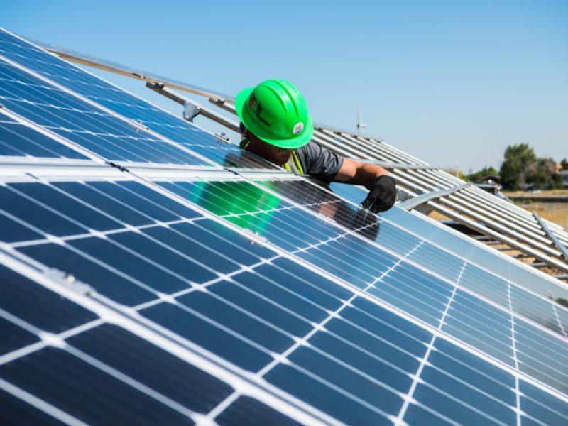 a worker in a green helmet installs a solar PV module on a rack