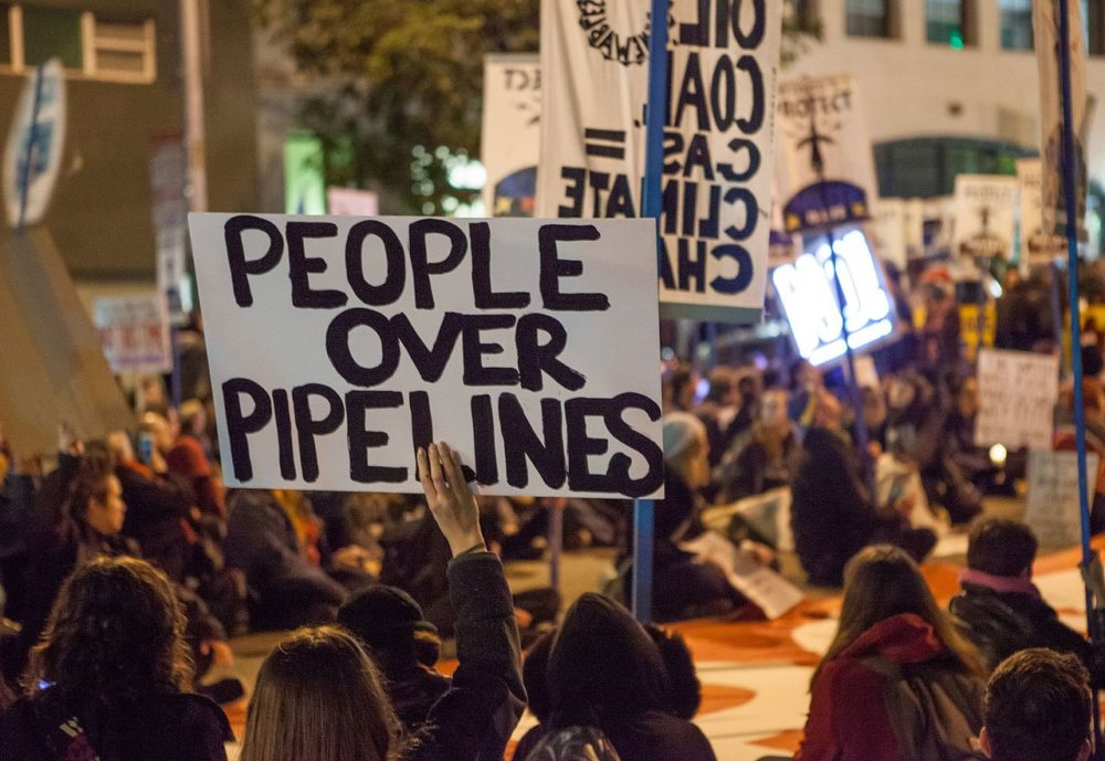 """a group of protesters: in the foreground, one holds a handwritten, black-on-white sign that reads """"PEOPLE OVER PIPELINES"""""""