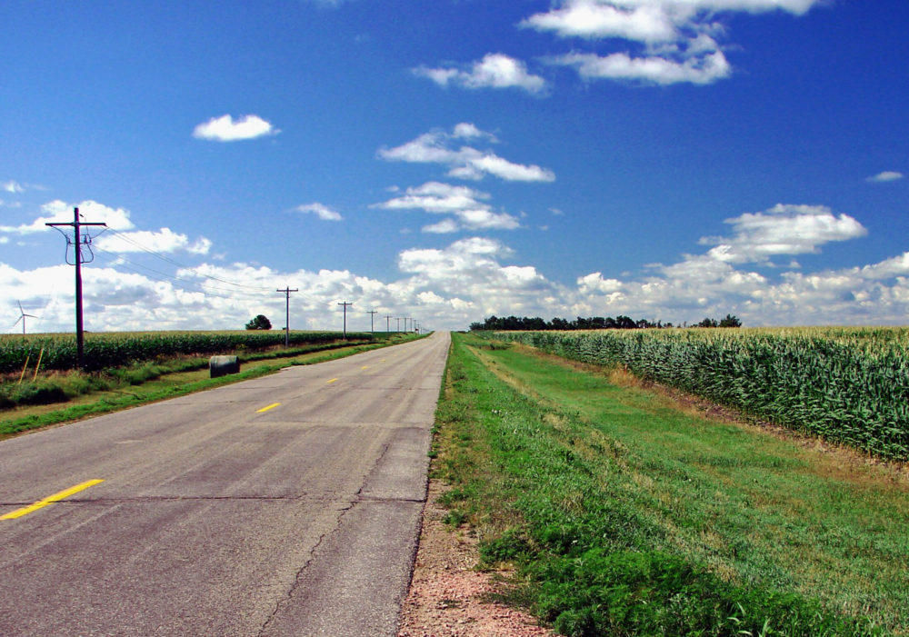 a highway surrounded by cornfields