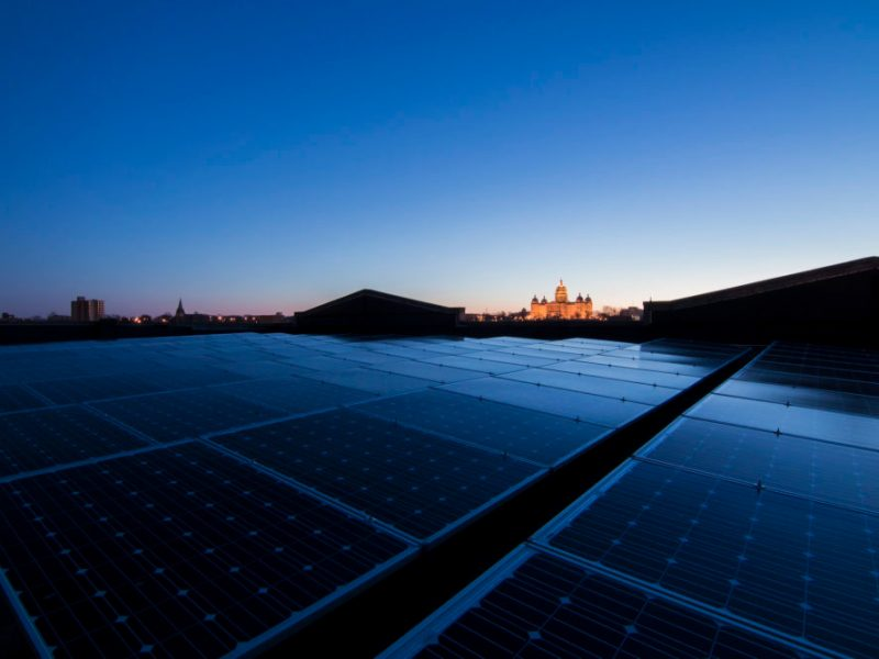 In the foreground, a series of solar panels on a rooftop; the Iowa State Capitol can be seen, illuminated, in the distance
