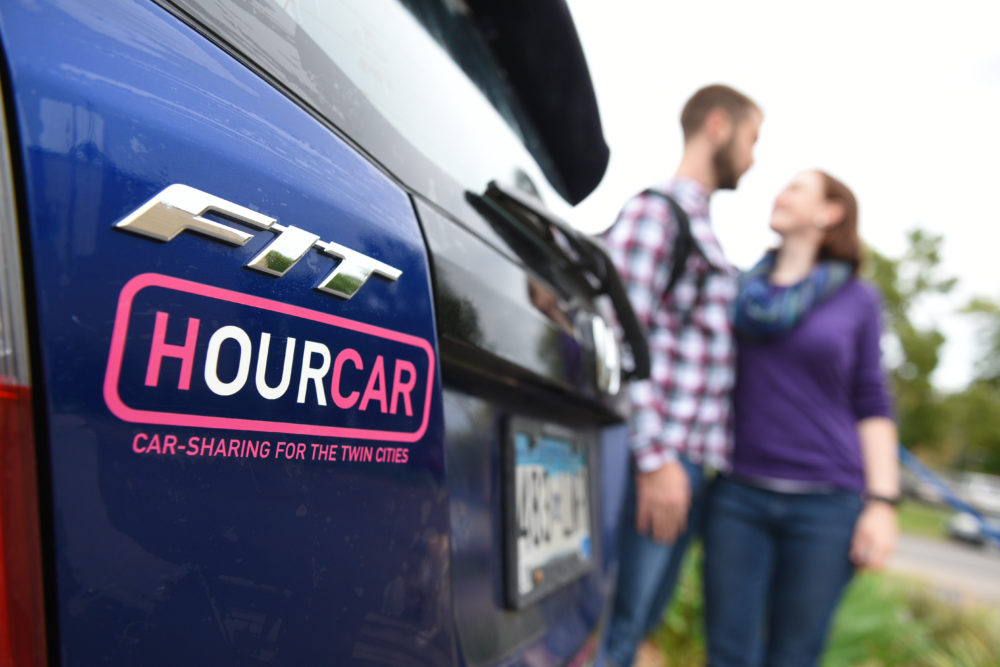 Closeup of the HourCar logo on the back of a blue car.