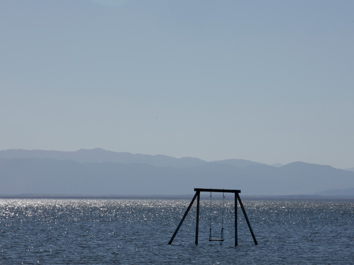 A swing set stands alone in the Salton Sea.