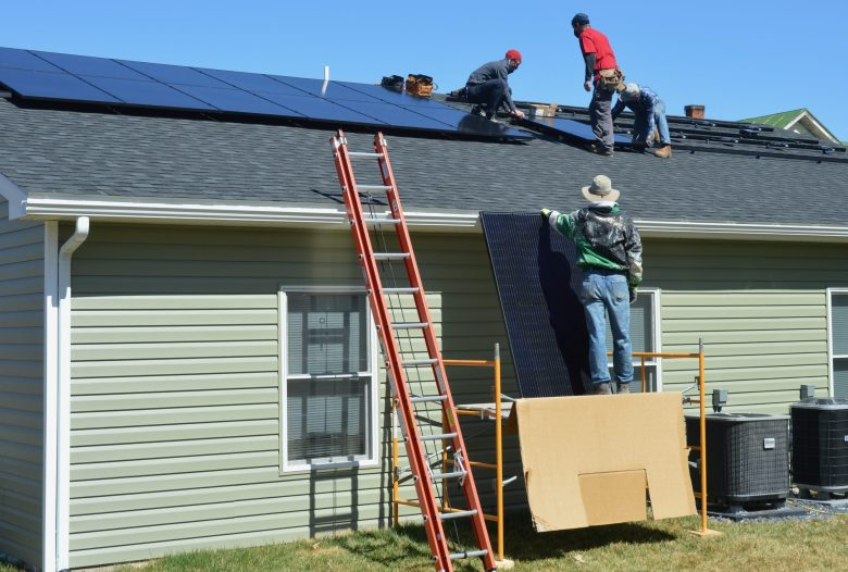 Workers install solar on a roof.