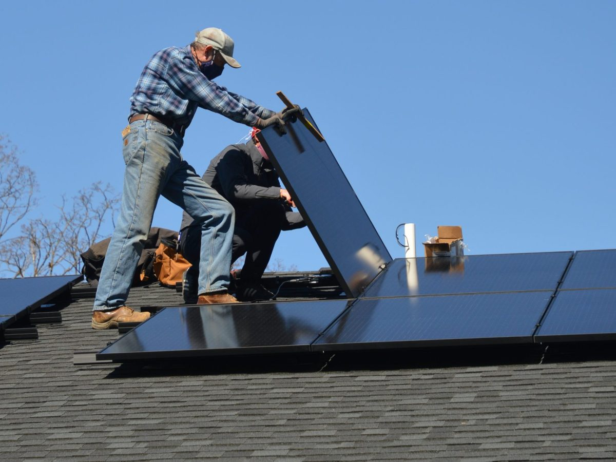 Two workers lower a rooftop solar panel into place.
