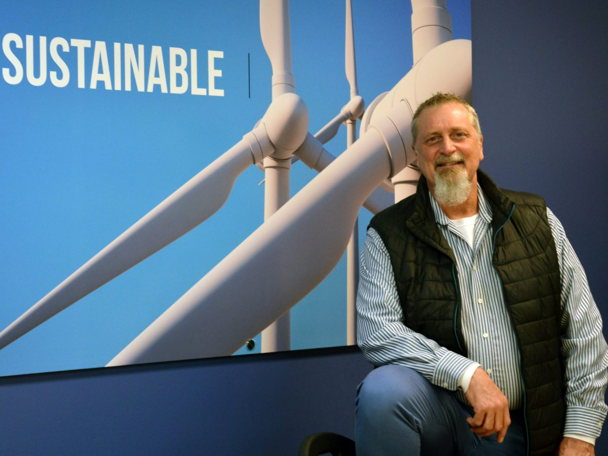 John Blumenstein poses in front of an image of wind turbines.