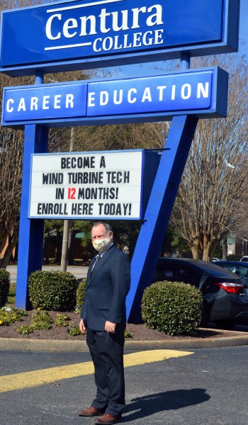 "Michael Lanouette stands in front of the Centura College sign, which reads ""Become a wind turbine tech in 12 months! Enroll here today!"""