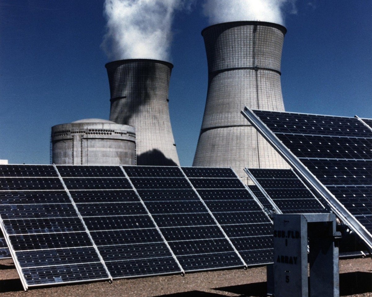 Solar panels in front of a nuclear plant.
