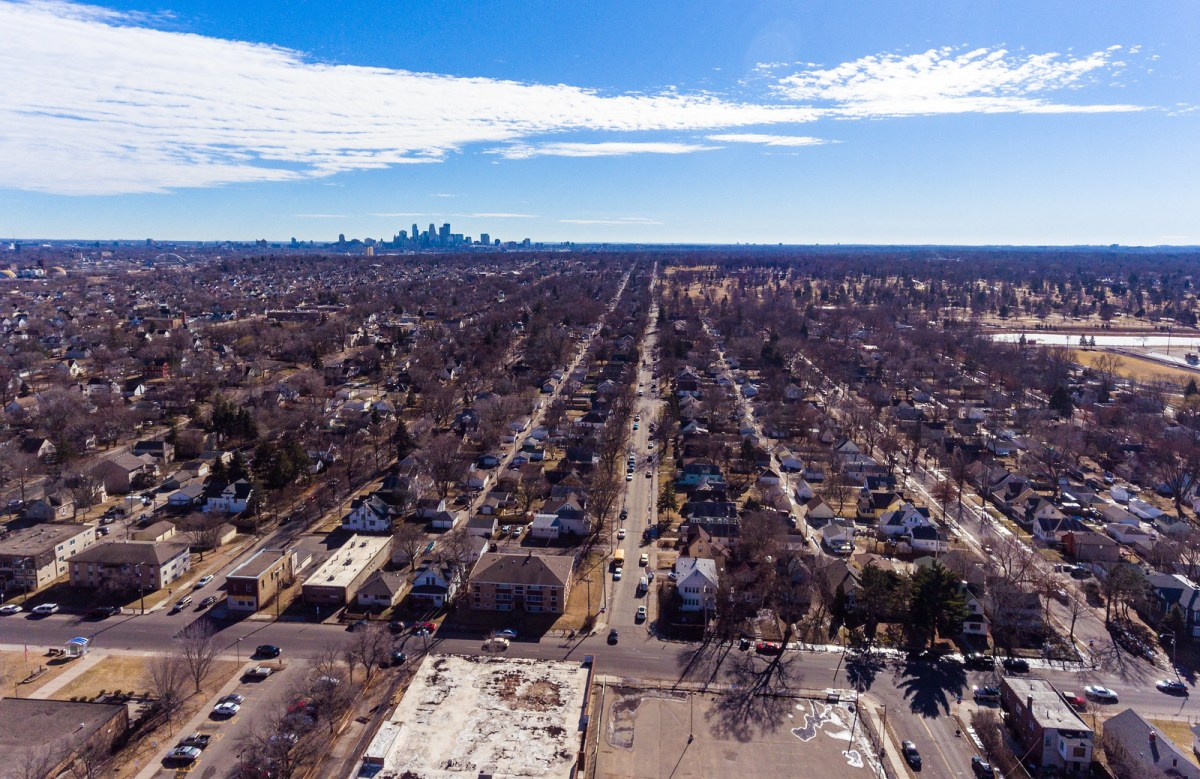 A drone photo of a Minneapolis neighborhood with the downtown skyline in the distance.