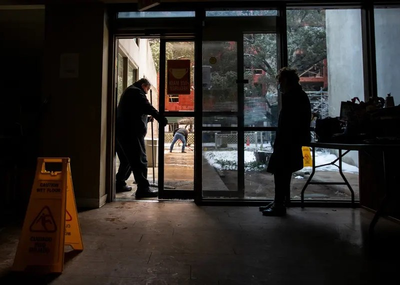 Two people wait inside a dark building in Texas. Snow is visible outside.
