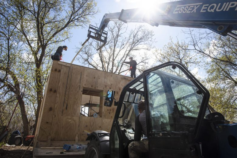 Construction workers assemble a prototype of a sustainably made and energy-efficient modular building made by New Frameworks in Winooski, Vermont, on Monday, April 19, 2021.