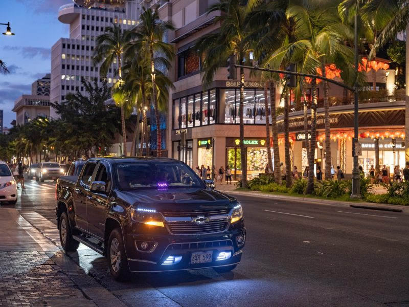 A black pickup truck with a Lyft sign in the window waits on a palm tree-lined street.