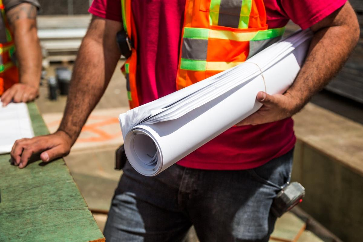 A person holding a roll of drafting paper