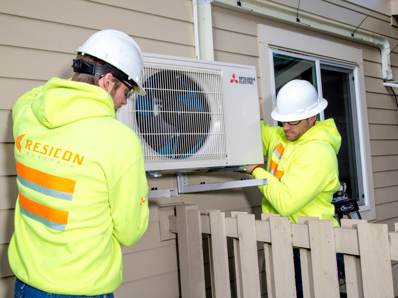 Construction workers help install a heat pump.