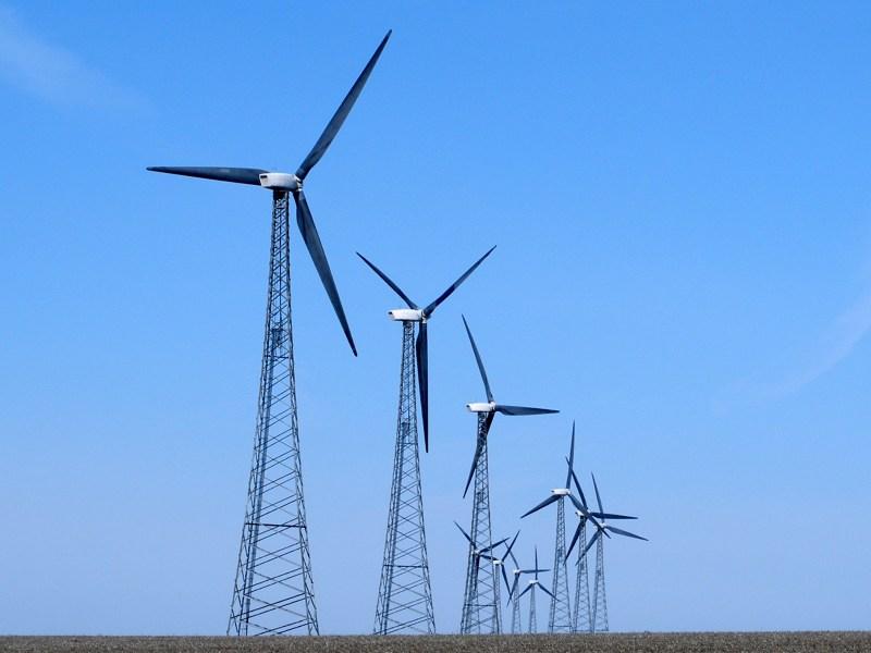 A row of wind turbines sit in a field.