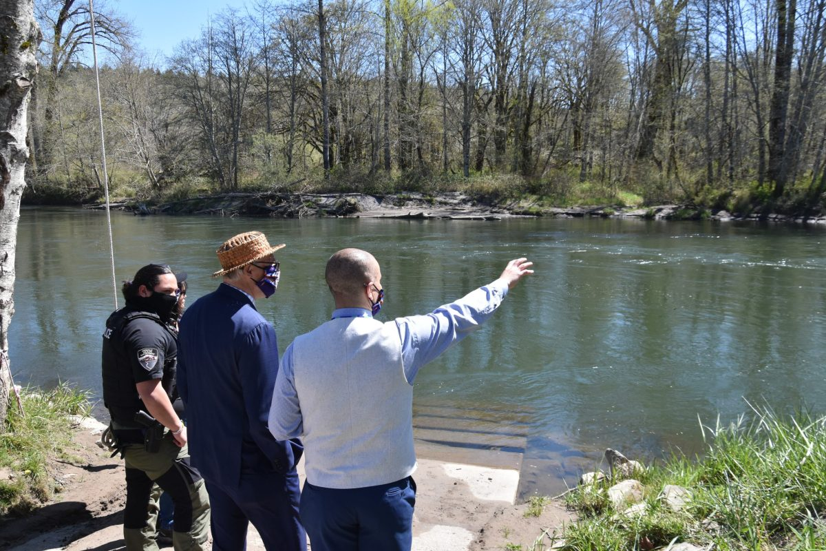 Gov. Jay Inslee looks over a river near the Wa He Lut Indian School in April 2021.