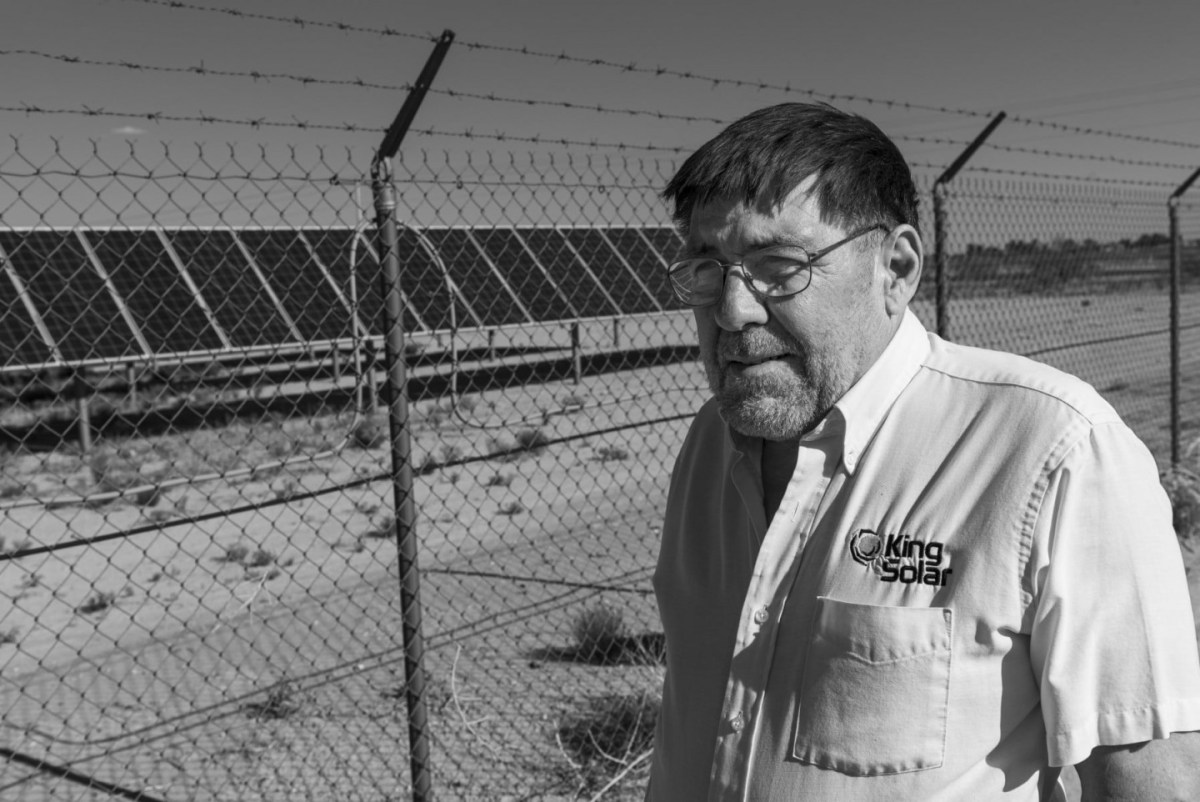 A man in a solar company shirt stands in front a barbed wire-surrounded solar array.