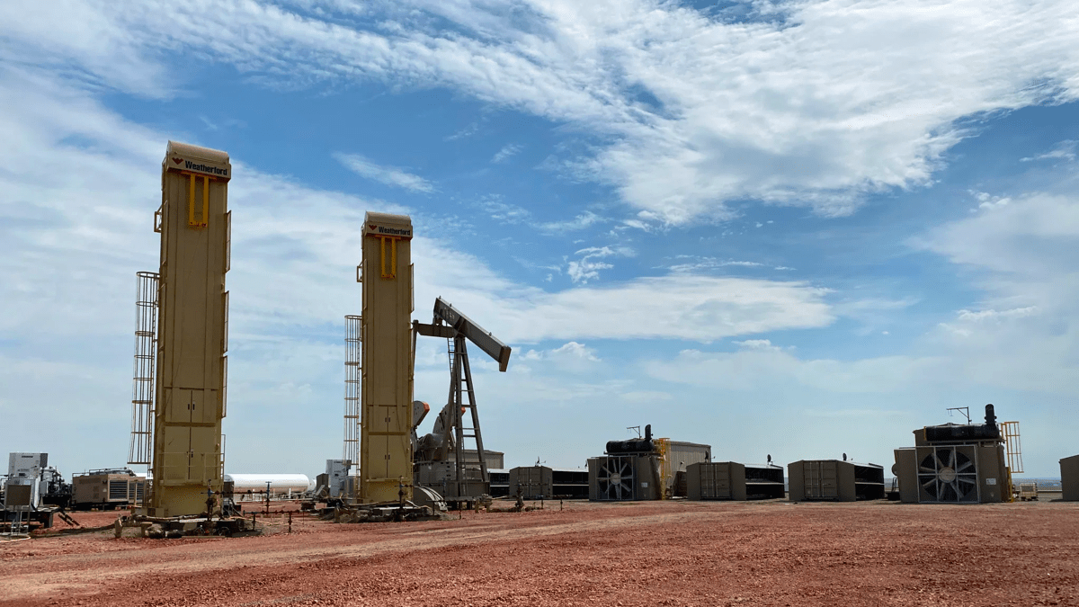 Oil wells sit on the reddish dirt under a blue sky in Montana.