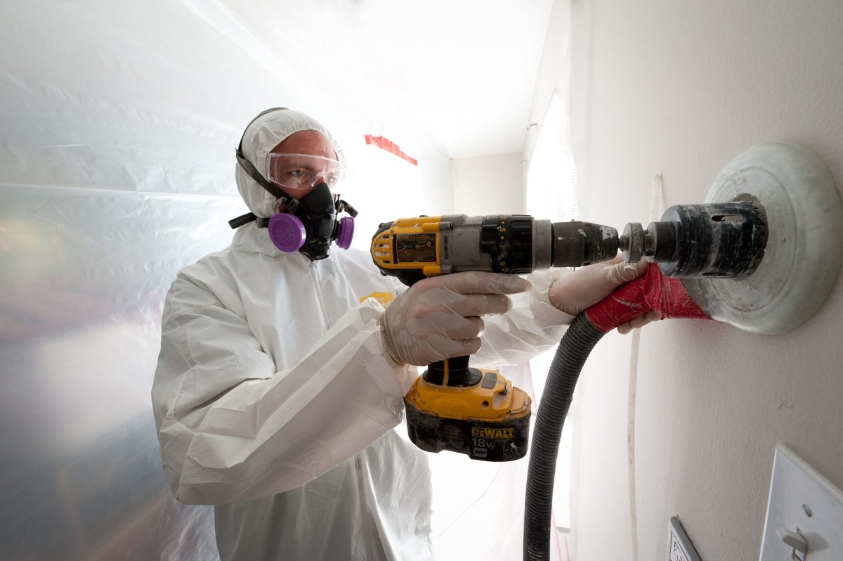 A weatherization worker drills holes to blow cellulose insulation in the interior walls of a Colorado home.
