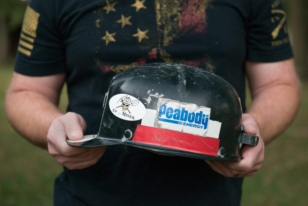 Brad Campbell holds his father Glen's hardhat at his home in Herrin, Illinois.