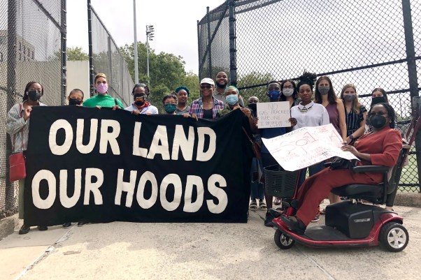 A group of people stand outside in New York City holding a banner that reads Our Land Our Hoods