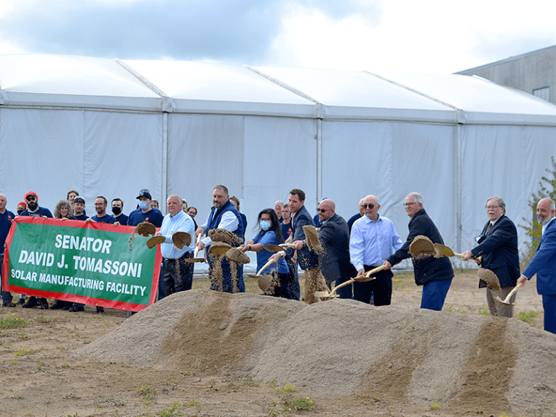 A group of people shovel a pile of dirt in a groundbreaking ceremony for a major solar panel factory expansion