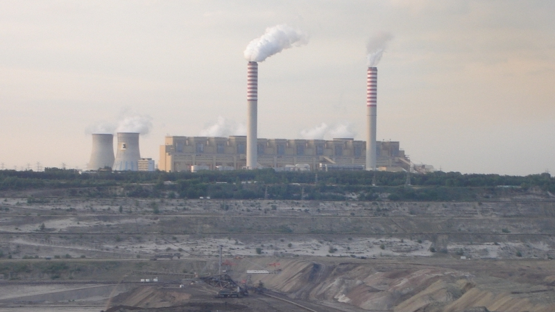 large coal plant with mine in foreground, smoke coming out of stacks, dark gray sky