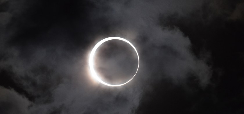 solar eclipse, sun behind clouds