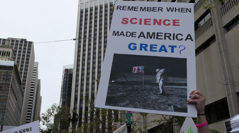 """Hand holding a sign that says """"Remember when science made america great?"""" with a picture of the man on the moon"""