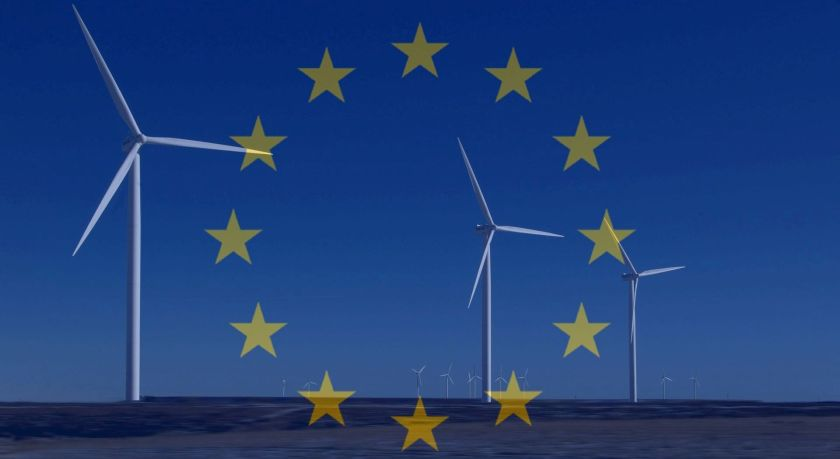 The EU flag laid over an image of wind turbines in a field