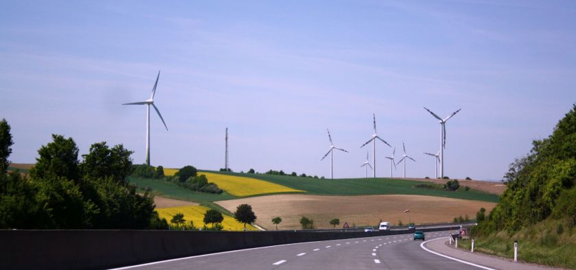 Wind turbines seen from the German highway in fields of yellow flowers