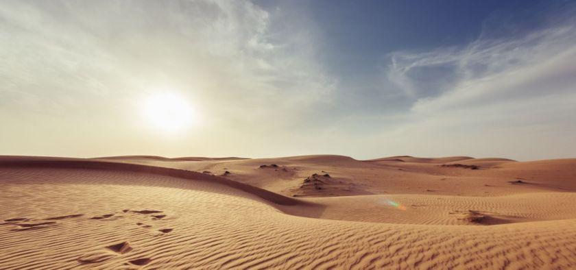 sun shining over the desert in a hazy sky