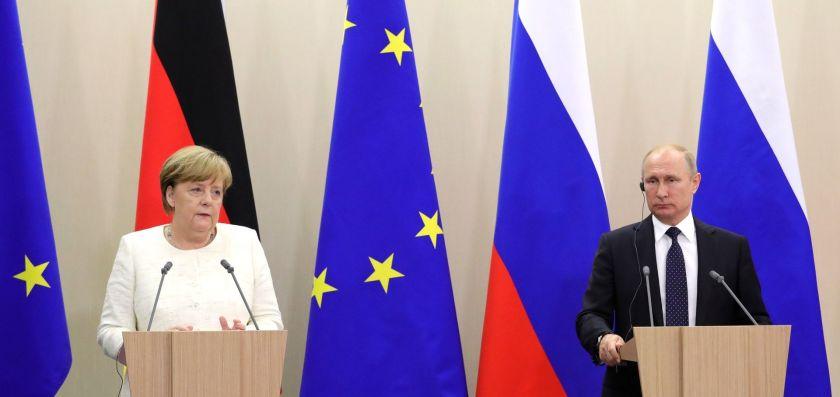 Angela Merkel and Vladimir Putin meet at Sochi with EU, Russian and German flags behind them