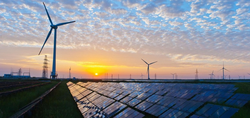 solar panels and wind turbines with sunrise reflecting on them