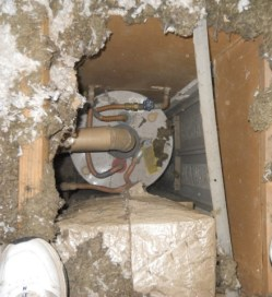 A furnace and water heater in a hall closet open to the attic