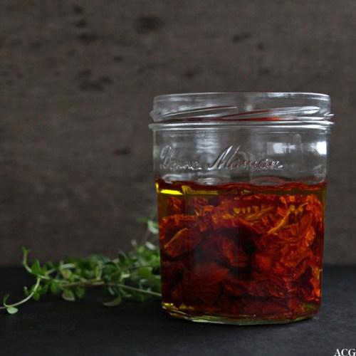 glass med semitørkede tomater i olje og en kvist timian