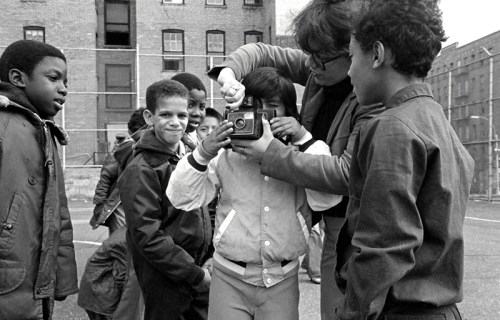 In the Fall of 1979, Perla de Leon and David Gonzalez taught a Visual Literacy workshop at two South Bronx schools. Here, Perla shows a student at CS 61 how to use a Polaroid camera. The images would then be put together in a story book written and illustrated by tams of young people.    CS61 was known for two things: it had a principal who actively encouraged the arts as an essential part of the curriculum. It was also one of the few remaining structures on Charlotte Street, the infamous urban wasteland visited by politicians and tourists.  Photo by David Gonzalez, All Rights Reserved 2009