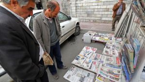 Iranians look at newspapers displayed on the ground outside a kiosk in Tehran on November 25, 2013. (AFP PHOTO/ATTA KENARE)