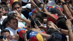 Leopoldo Lopez, left, an ardent opponent of Venezuela's socialist government led by President Nicolas Maduro, is surrounded by supporters during a demonstration before turning himself in to authorities, in Caracas, on February 18, 2014. (AFP Photo/Raul Arboleda)