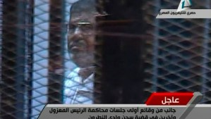 Deposed Egyptian President Mohamed Mursi of the Muslim Brotherhood stands inside his glass cage during his trial at a Cairo police academy January 28, 2014. Mursi went on trial on charges in connection with a mass jail break during the 2011 uprising, state television reported. REUTERS/Egyptian State TV via Reuters TV (EGYPT - Tags: POLITICS CRIME LAW) NO SALES. NO ARCHIVES. FOR EDITORIAL USE ONLY. NOT FOR SALE FOR MARKETING OR ADVERTISING CAMPAIGNS. EGYPT OUT. NO COMMERCIAL OR EDITORIAL SALES IN EGYPT